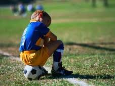 Sad kid on soccer ball