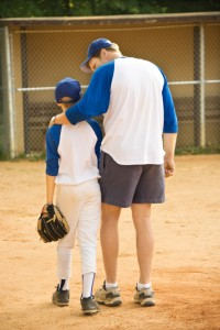 Coach reassuring young baseball player